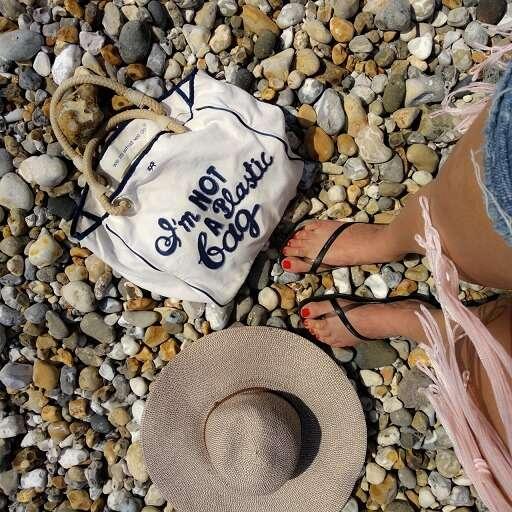 岸辺に立つ少女の足元(シンプルなエコバッグと麦藁帽)