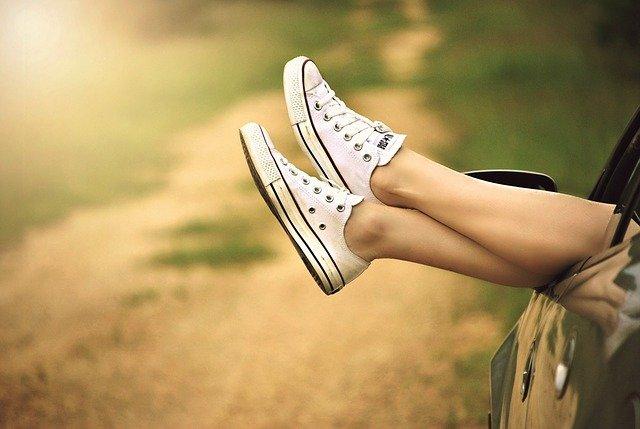 スニーカー(荒野を走る車の窓から出した女性の足)